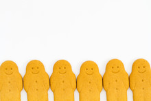 A Row Of Gingerbread Men Smiling And Looking Happy At The Bottom Of The Frame And On An Isolated White Background.