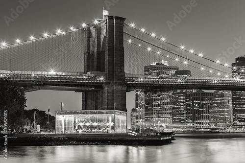 Black and White of  Brooklyn Bridge Tower at twilight with carousel and skyscrapers of Lower Manhattan. Financial District. New York City