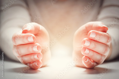 Foto Light between woman's hands in gesture of protection, care.
