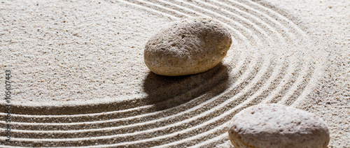 Foto op Plexiglas Stenen in het Zand zen sand still-life - textured stones set on sinuous waves for concept of steadiness or suppleness with inner peace