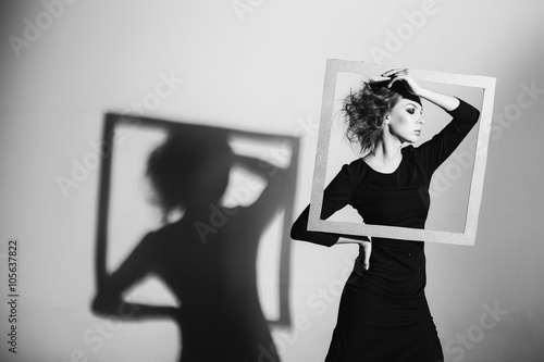 Photo  Сharismatic woman frame in his hands, fashion pose, black and white photo, stud