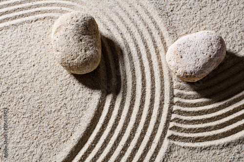 Photo sur Plexiglas Zen pierres a sable zen sand still-life - two stones across lines to give different directions for concept of change or flexibility with peace, top view