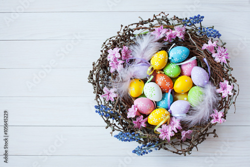 Photo  Easter nest with eggs and flowers on a light wooden background, candy and toy ra