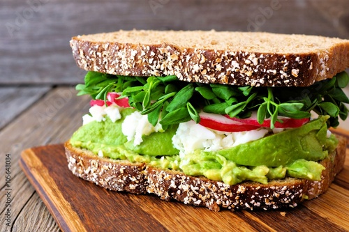 In de dag Snack Superfood sandwich with whole grain bread, avocado, egg whites, radishes and pea shoots on wood board
