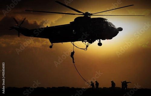 Fotografering  Helicopter dropping soldier during sunset