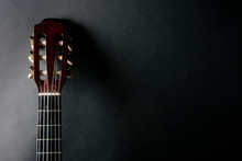 Neck Of An Old Acoustic Guitar On A Black Background (with Copy Space For Your Text)