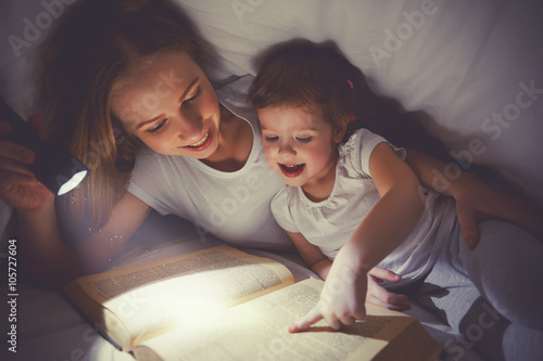 Photo Family reading bedtime. Mom and child reading book with a flashl