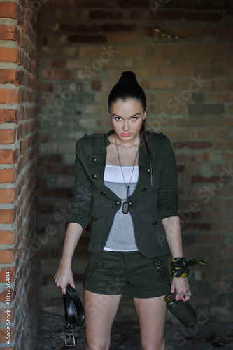 фотография  Girl near the brick wall in military style. Lara Croft style.