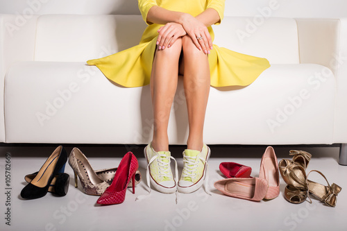 Fotografia  Woman sitting on couch and trying on shoes
