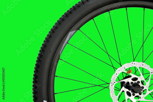 Koło rowerowe na zielonym tle.