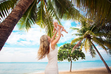 Young Mother And Cute Baby Playing On Tropical Beach