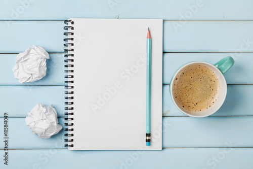 Fotografie, Obraz  Coffee mug, clean notebook, pencil and crumpled paper on blue rustic table from