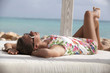 Beach woman in summer dress enjoying the summer sun