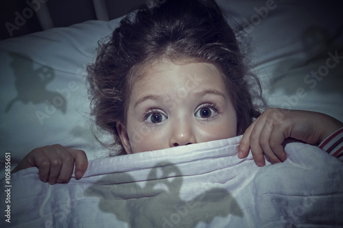 Photo  scared cute little girl under the blanket in her bed