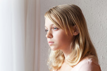 Caucasian Girl Near A Window With White Curtains