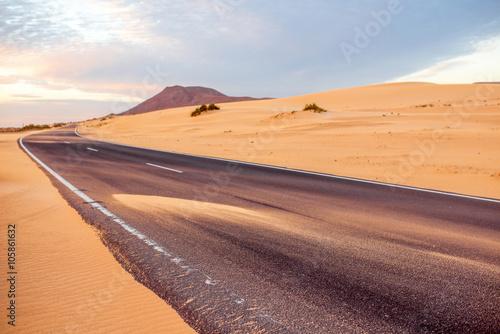 Poster de jardin Desert de sable Sandstorm on the desert road on Corralejo dunes on Fuerteventura island in Spain