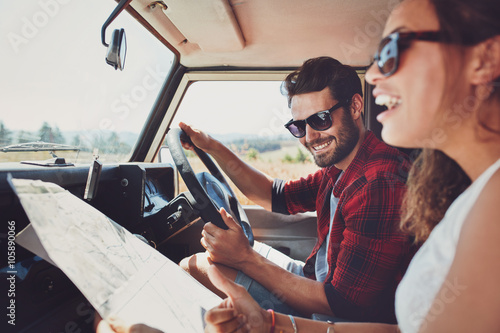Fotografia  Happy young couple with a map in the car