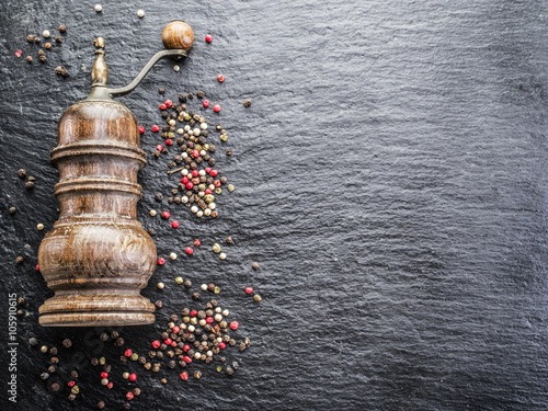 Fotomural Colorful peppercorns and old pepper mill on the black background