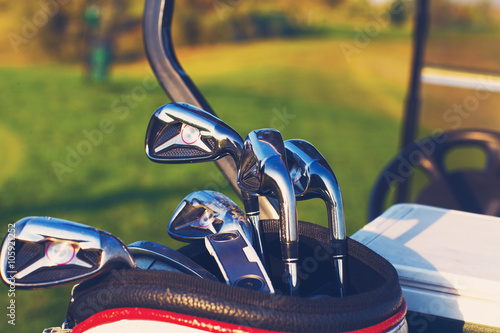 Golf clubs drivers over green field background - 105921252