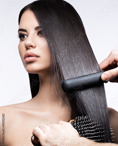 Fotografija Beautiful brunette girl with a perfectly smooth hair, curling and classic make-up