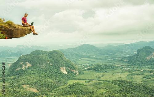 obsluguje-dzialanie-z-laptopu-obsiadaniem-na-skalistej-gorze-na-pieknym-scenicznym-clif-tle-tajlandia-krabi