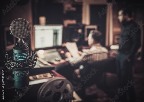 Photo  Sound engineer and producer working together at mixing panel in the boutique recording studio