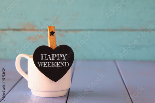 Fotografía  cup of coffee and little heart shape chalkboard with the phrase: HAPPY WEEKEND