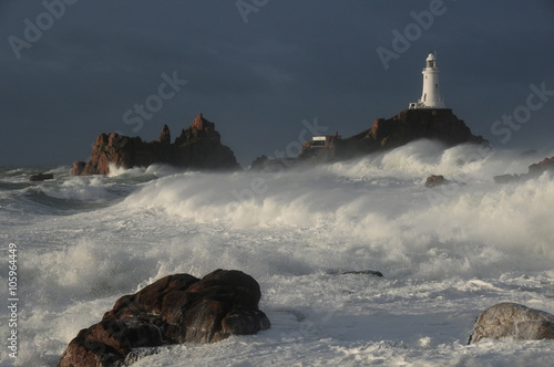 Montage in der Fensternische Leuchtturm La Corbiere lighthouse, Jersey, U.K. Coastal structure in extreme weather stormy conditions.