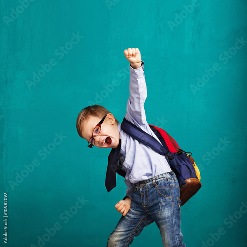 Fototapeta smiling little boy with big backpack jumping and having fun obraz