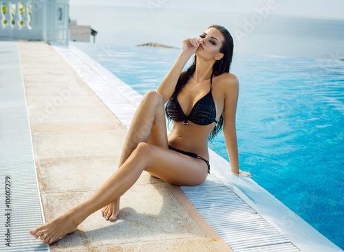 Obraz Beautiful woman wearing black bikini by the pool in summer scene - fototapety do salonu