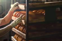 Seller Puts Bread On The Shelf.