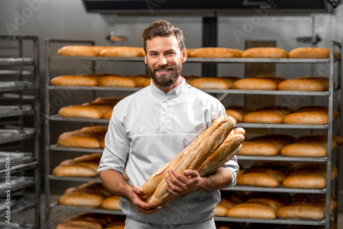 Fotografia, Obraz Handsome baker in uniform holding baguettes with bread shelves on the background