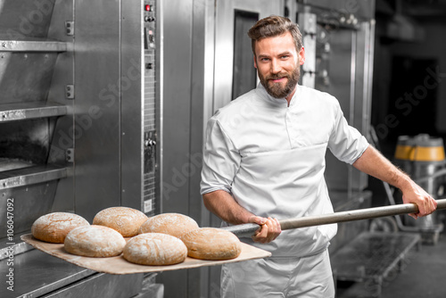 Foto op Aluminium Bakkerij Handsome baker in uniform taking out with shovel freshly baked buckweat bread from the oven at the manufacturing