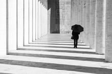 Donna Con Ombrello In Un Corridoio Porticato In Bianco E Nero