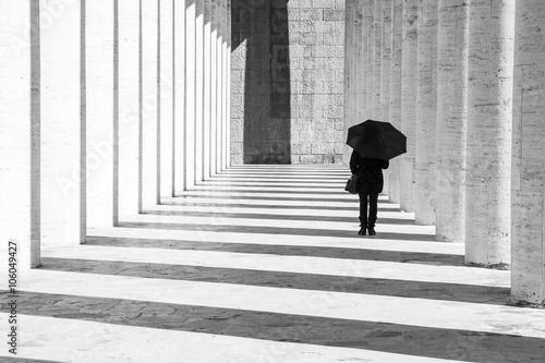 Fotografia  Donna con ombrello in un corridoio porticato in bianco e nero