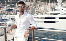 Handsome Male Model Posing In Front Of A Luxury Yacht During Sum