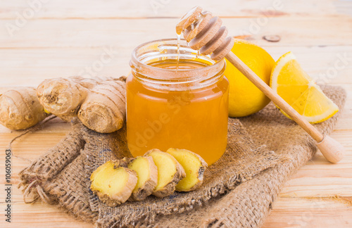 Photo  Honey comb, fresh lemon and ginger on a wooden table