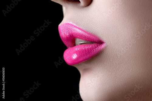 Photographie  Closeup macro photo of pretty natural lips with pink glossy lipstick on black background