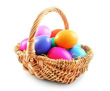 Multicoloured Easter Eggs In Wicker Basket Isolated On White