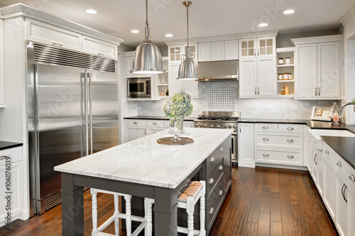 Photo  Beautiful Kitchen in Luxury Home with Island, Hardwood Floors, and Stainless Ste