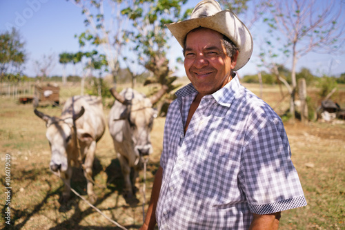 Fotografía  Portrait Happy Man Farmer At Work With Ox Looking At Camera