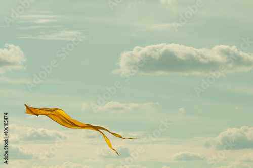 Fototapeta Yellow kite flying in the cloudy sky