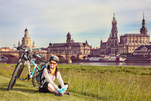 Adult Attractive Female Cyclist Sitting On The Grass And Resting. The Happy Woman Sits At The Old City Background And Looks At The Camera. So-called The Balcony Of Europe, Dresden, Germany