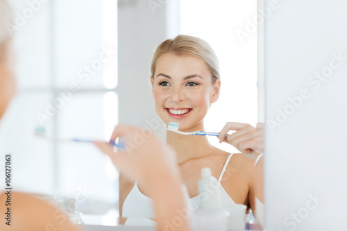 Valokuva  woman with toothbrush cleaning teeth at bathroom