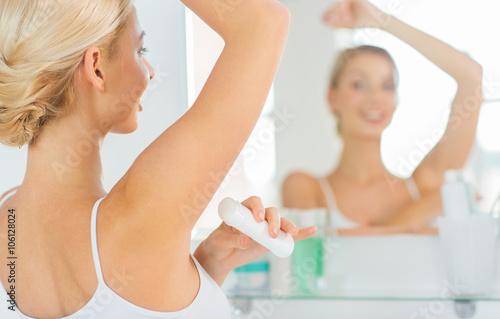woman with antiperspirant deodorant at bathroom Canvas Print