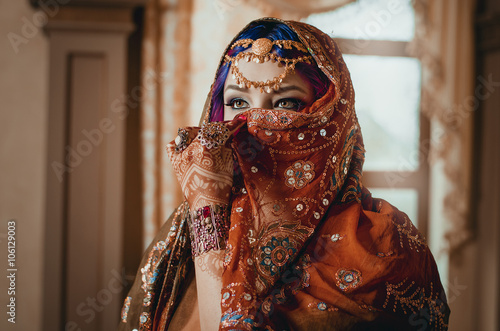 fototapeta na lodówkę portrait of a beautiful young woman in traditional Indian ethnic dress and painted ational patterns on the hands, mehendi. girl covers her face with a handkerchief