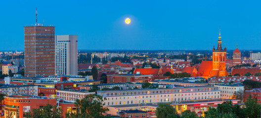 FototapetaAerial panorama of modern city and Old Town with Church of Saint Catherine at moonlight night in Gdansk, Poland