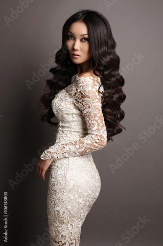 Foto  sensual asian woman with long dark hair in elegant lace dress