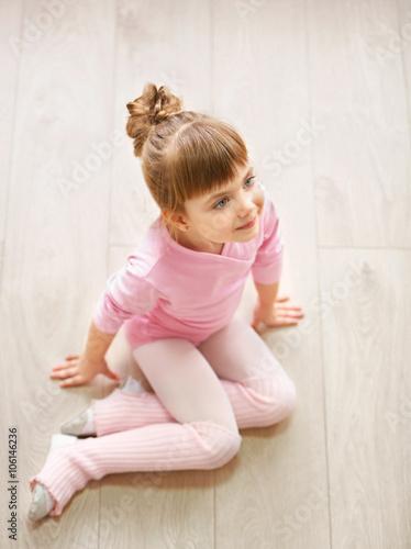 f45810f2ea69 Little cute girl in pink leotard sitting on floor at dance studio ...