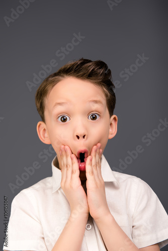 Close up portrait of little shocked boy touching his face Wallpaper Mural
